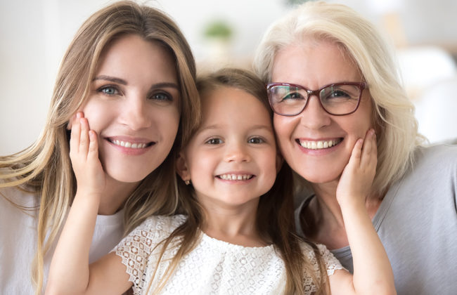 Grandmother, mother and daughter smiling